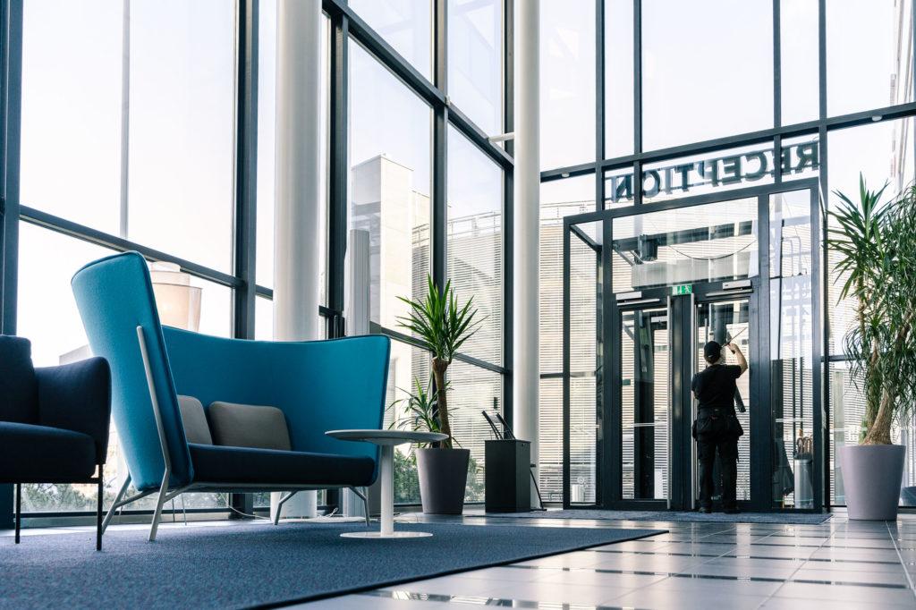 Henkilö siivoamassa modernin toimistorakennuksen lasisia ulko-ovia